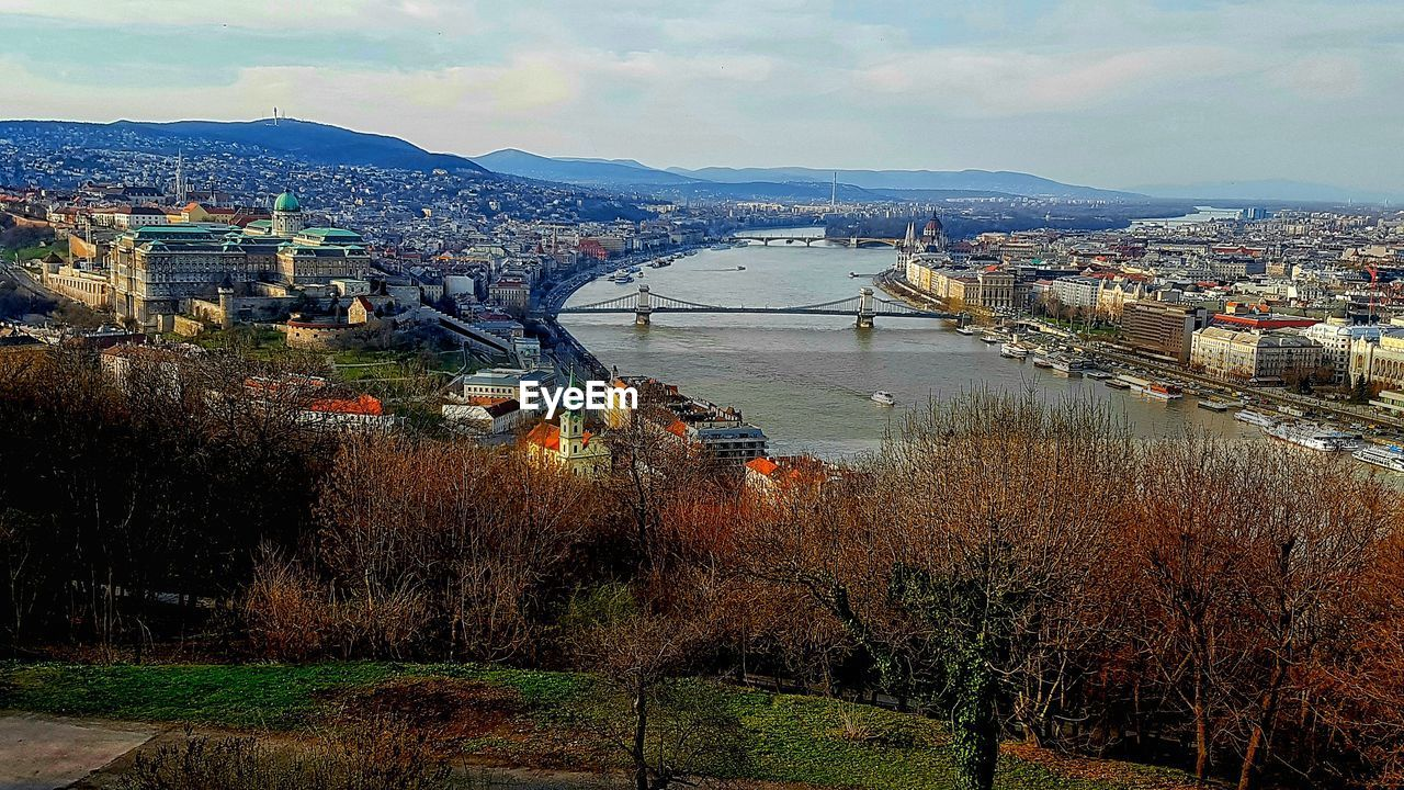 architecture, built structure, city, building exterior, cityscape, bridge - man made structure, water, river, connection, transportation, high angle view, no people, sky, outdoors, day, suspension bridge, travel destinations, chain bridge, tree, mountain, nature