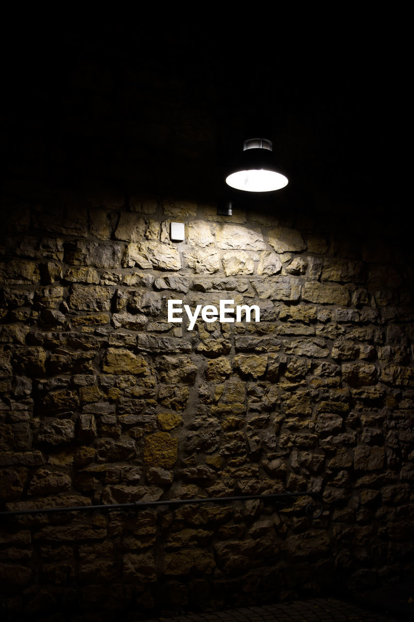 lighting equipment, illuminated, wall, brick, no people, light, wall - building feature, indoors, brick wall, electric lamp, electricity, dark, night, light - natural phenomenon, electric light, light bulb, textured, glowing, architecture, close-up, stone wall, light fixture, ceiling