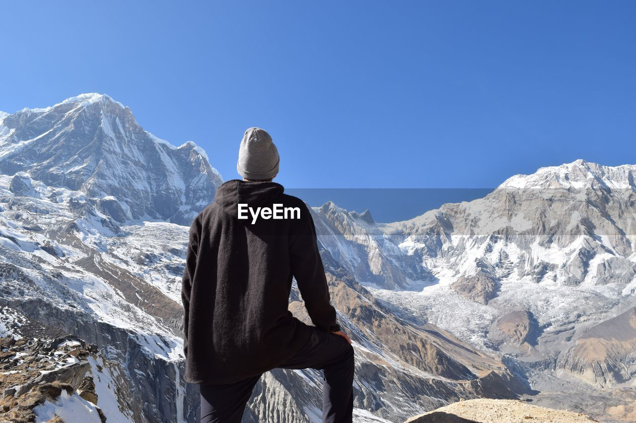Rear View Of Man Against On Snowcapped Mountains