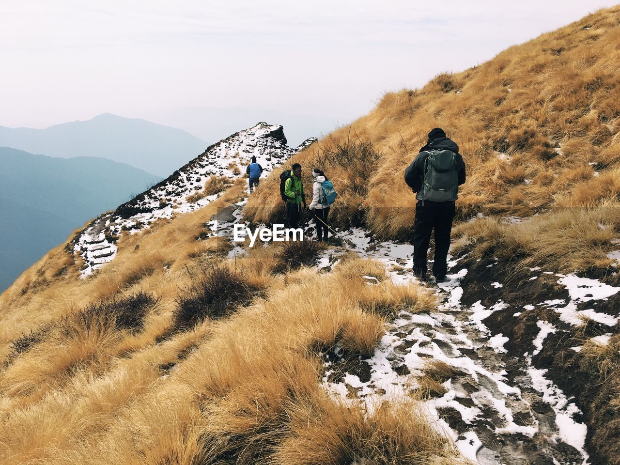 REAR VIEW OF PEOPLE ON MOUNTAINS AGAINST SKY