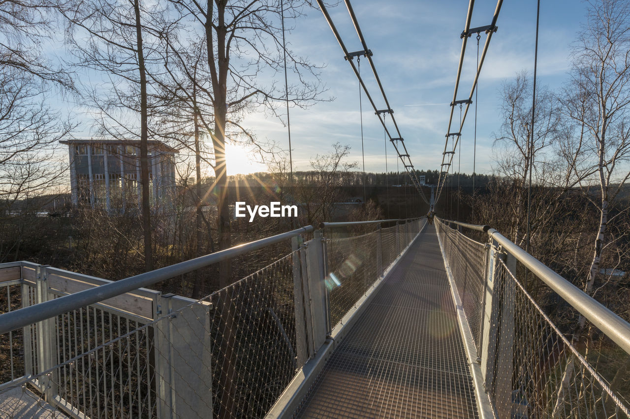 sky, tree, plant, architecture, nature, railing, built structure, day, no people, cloud - sky, bare tree, the way forward, transportation, sunlight, metal, direction, connection, outdoors, bridge, sunset, track