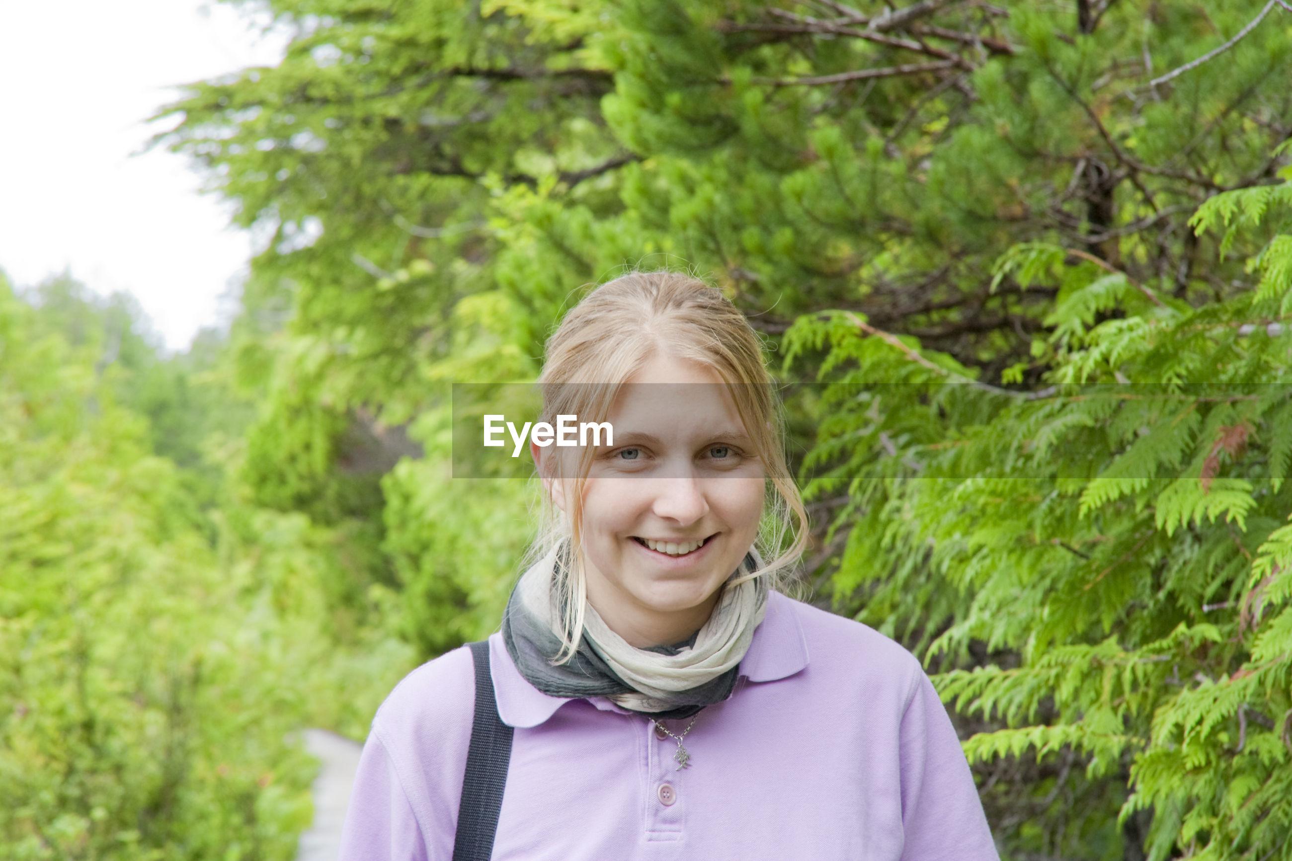 Portrait of teenage girl against trees