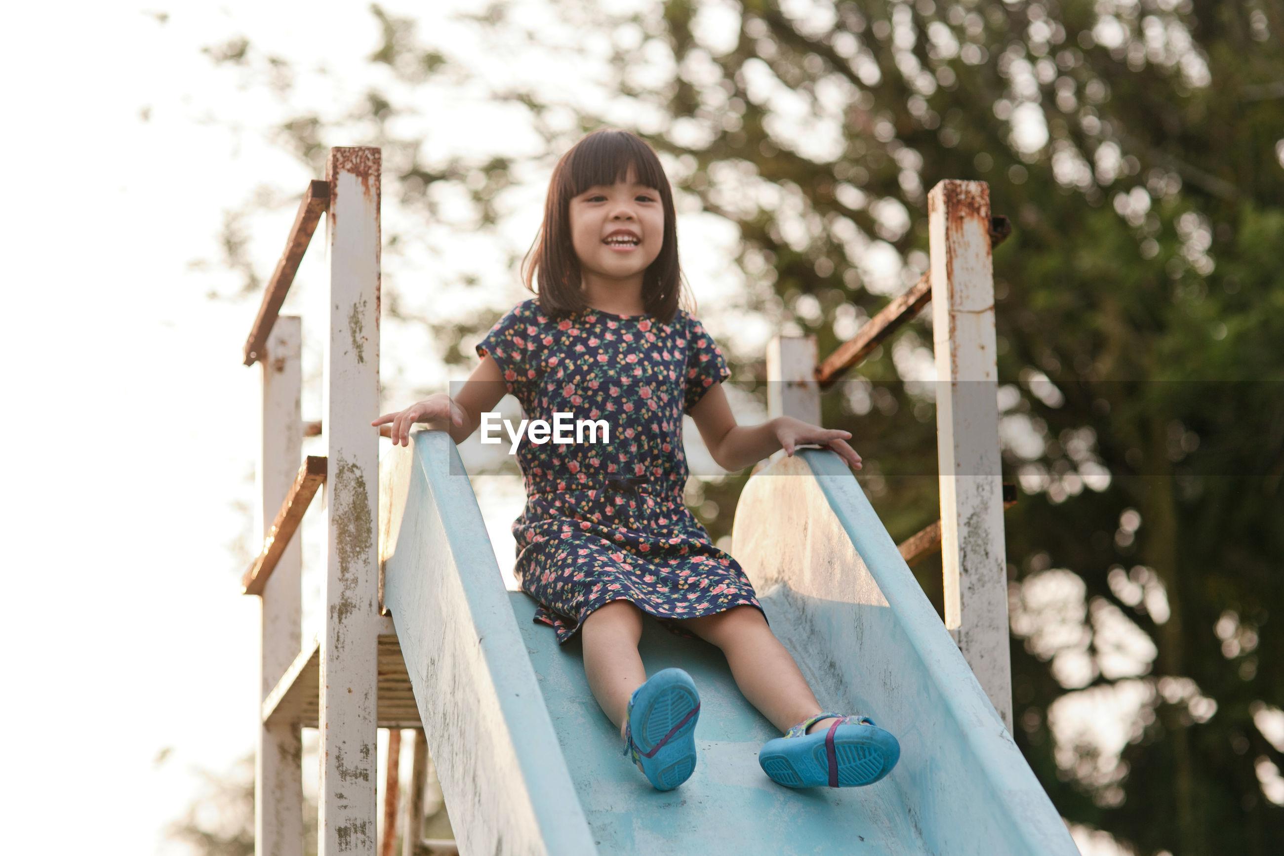 Portrait of girl sliding down on slide in park