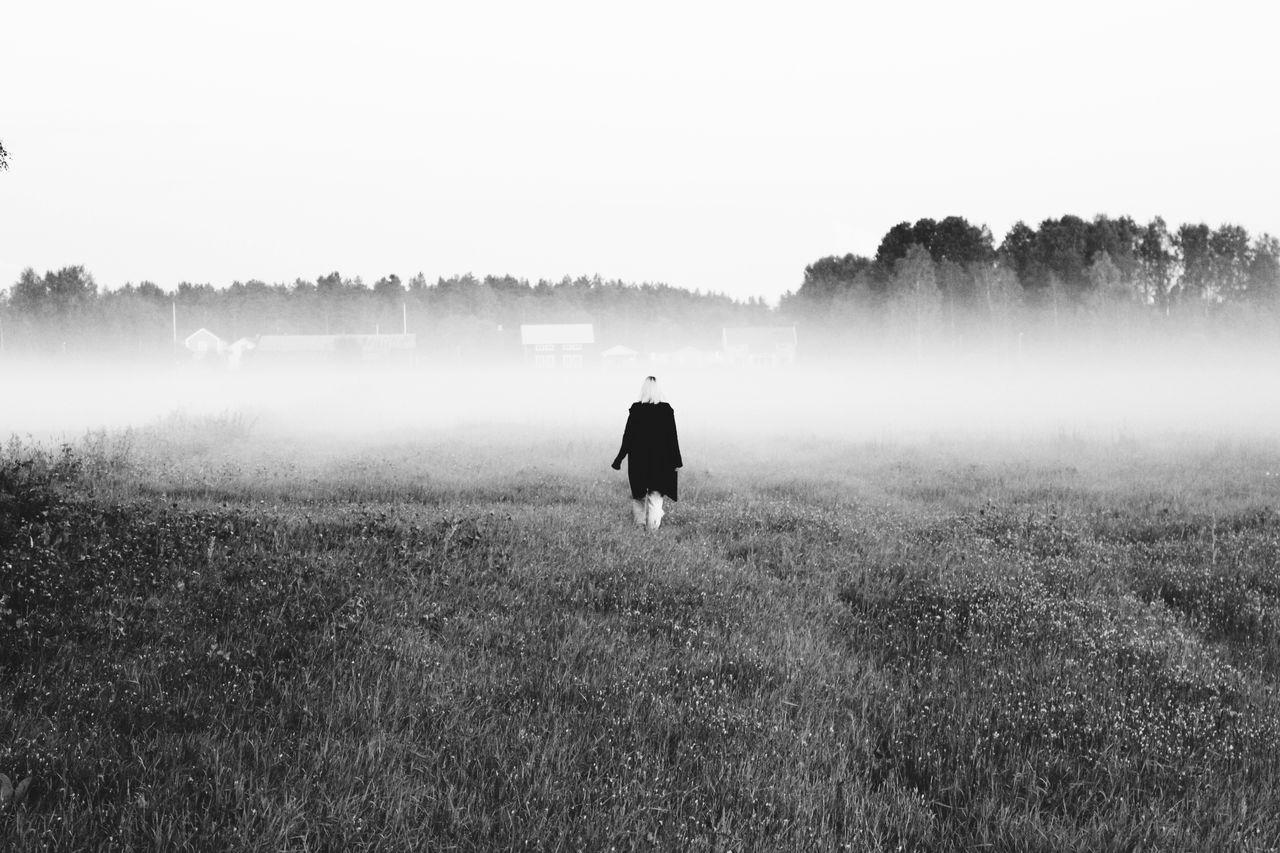 Rear View Of Woman Walking On Grass Field