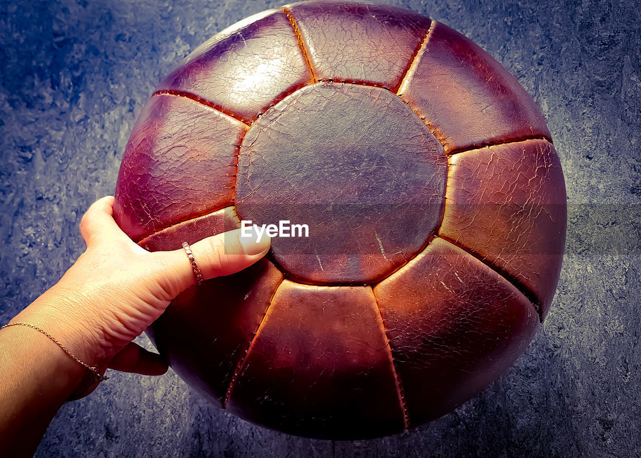 human hand, ball, human finger, human body part, real people, holding, one person, sport, soccer ball, close-up, leisure activity, outdoors, soccer, lifestyles, day, people