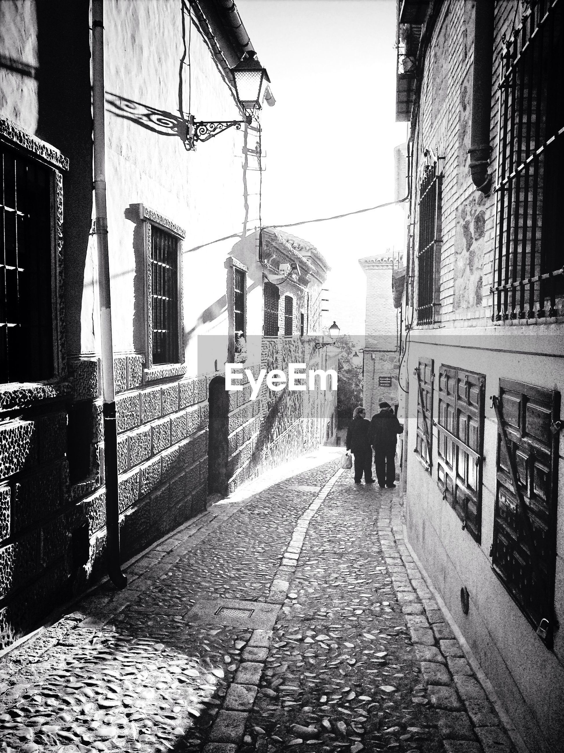 Rear view of couple walking on narrow cobbled street