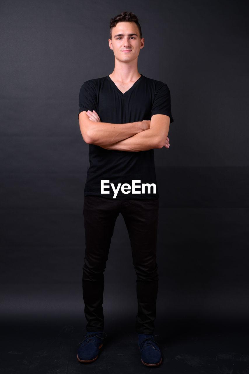 Full length portrait of man standing against black background