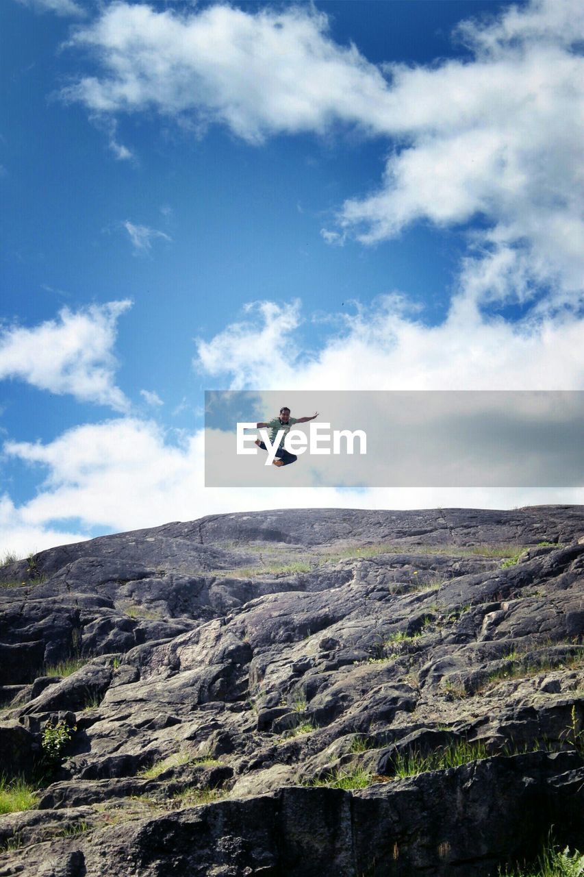 Man Jumping Over Rocky Field Against Sky