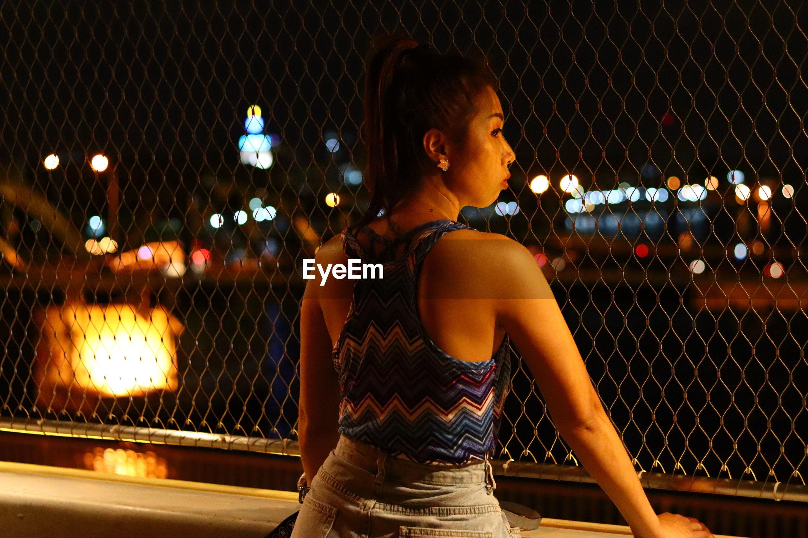 Woman looking at illuminated city at night