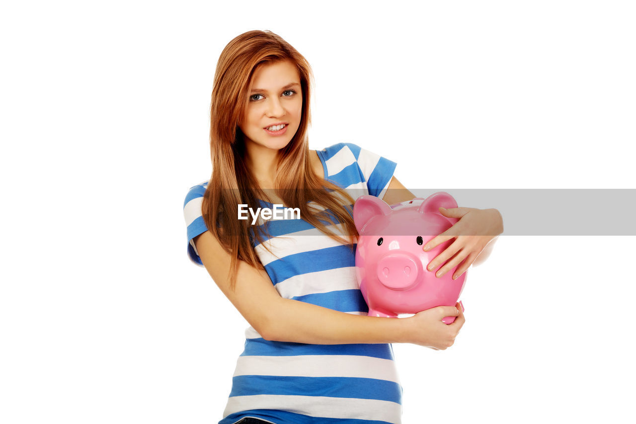 Portrait of young woman holding piggy bank while standing against white background