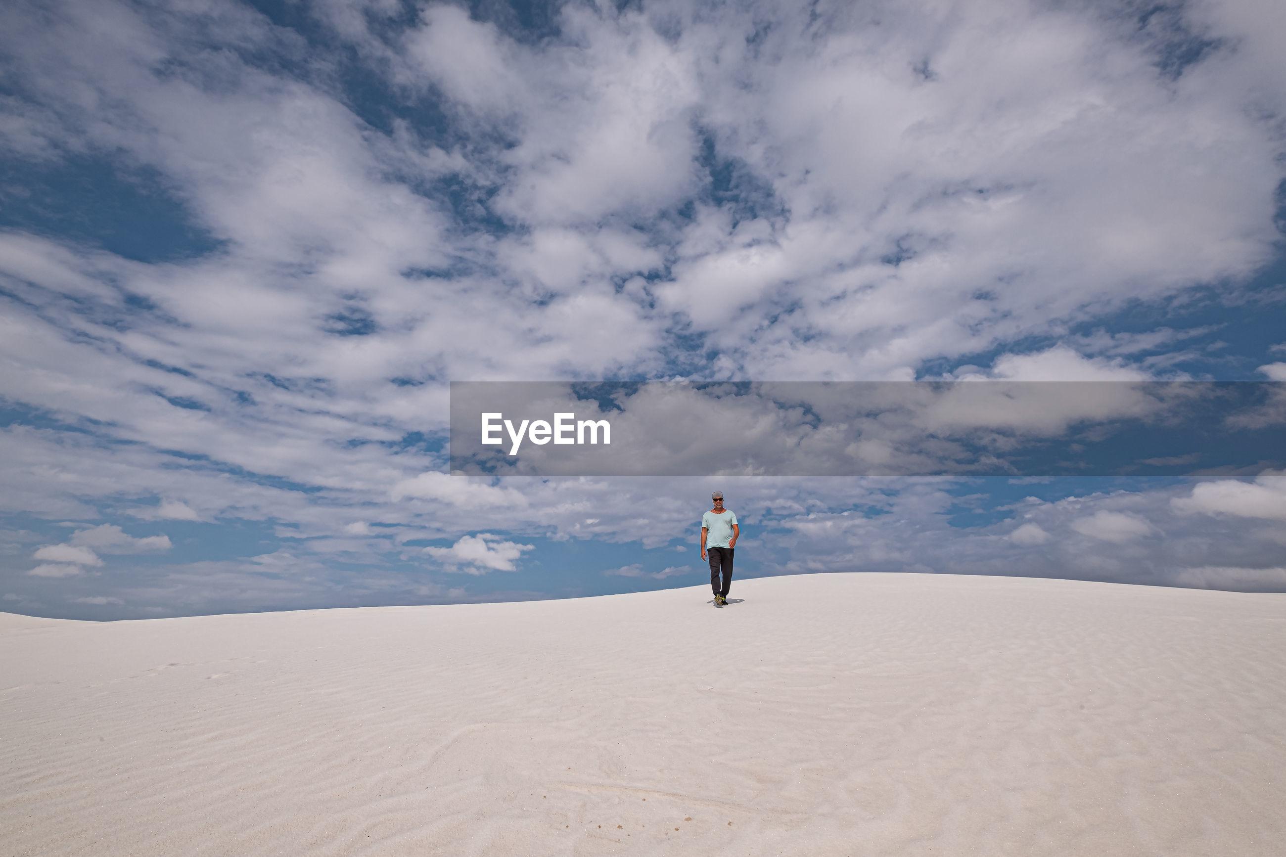 Man walking on sand at desert against sky