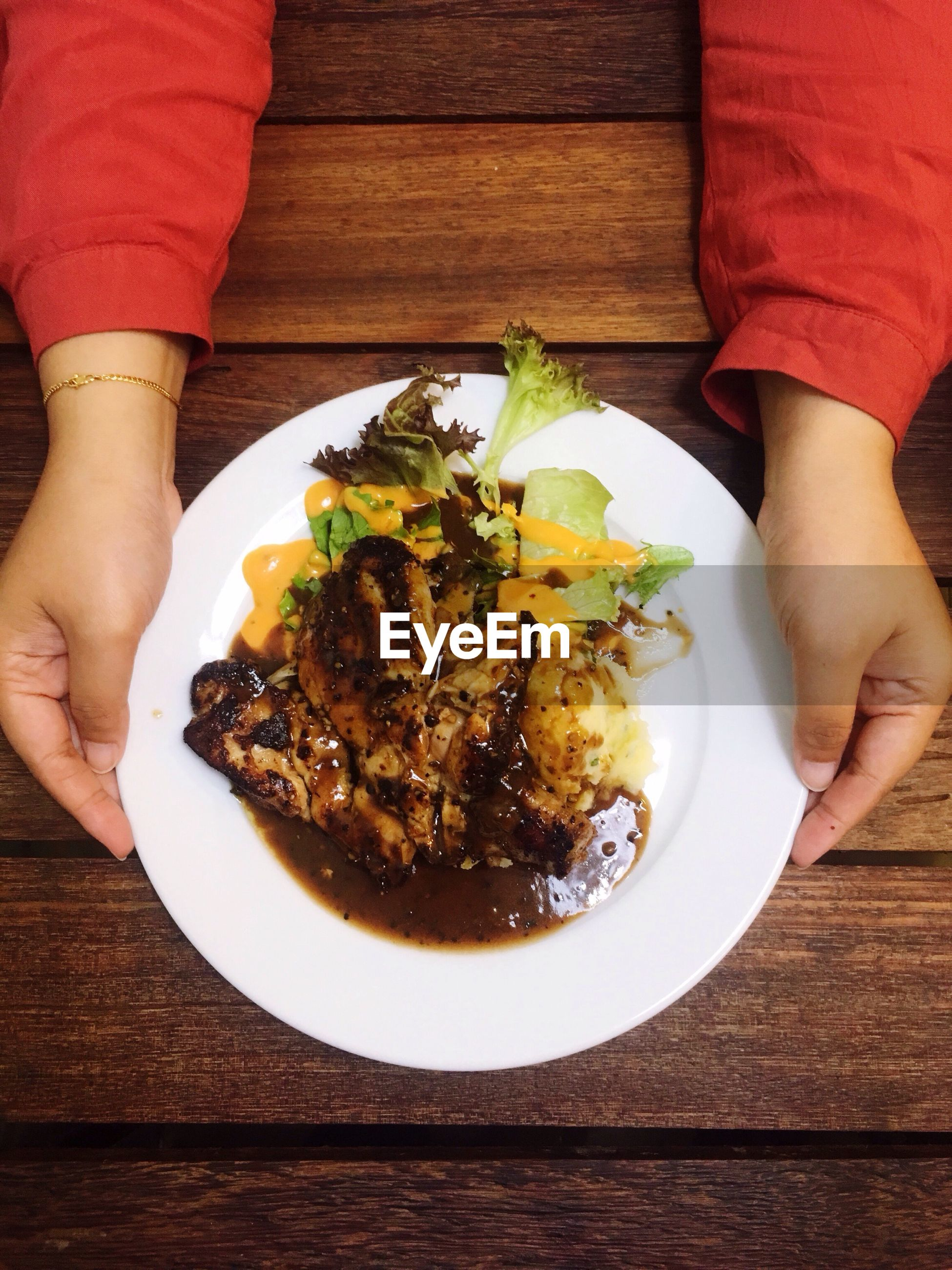 Cropped hands holding food in plate over table