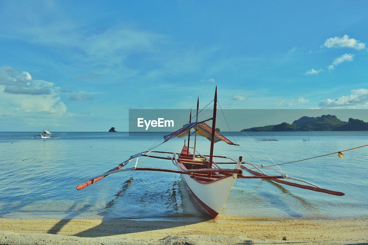 Outrigger Canoe Moored On Sea Against Sky