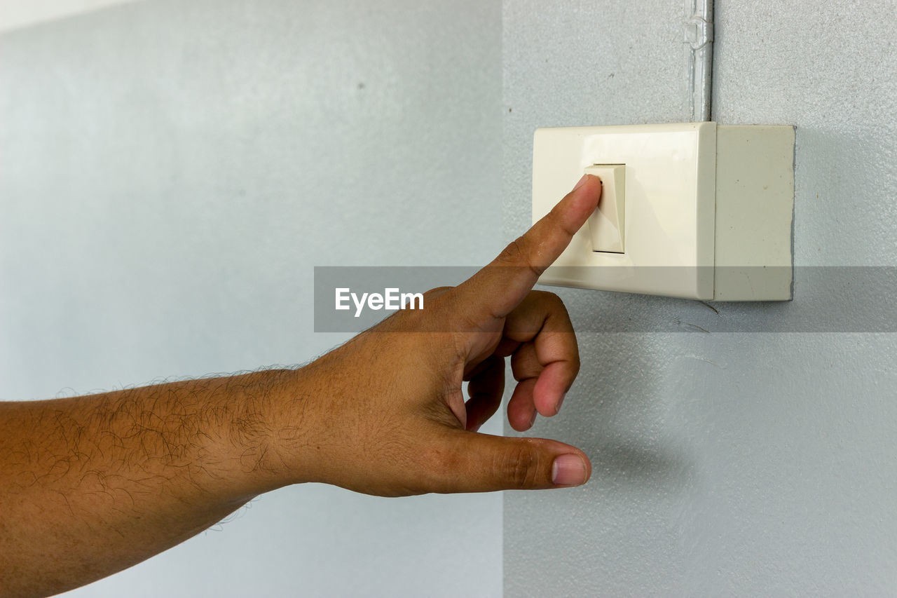 Cropped hand of man pressing switch button