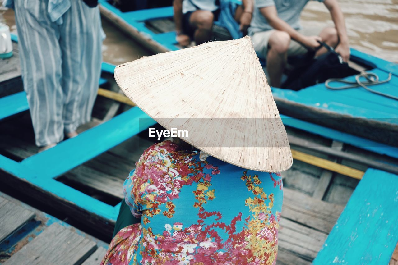 Rear view of woman wearing asian style conical hat in boat