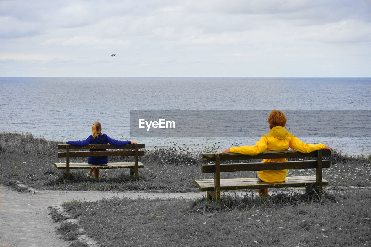 REAR VIEW OF PEOPLE SITTING ON BENCH LOOKING AT SEA