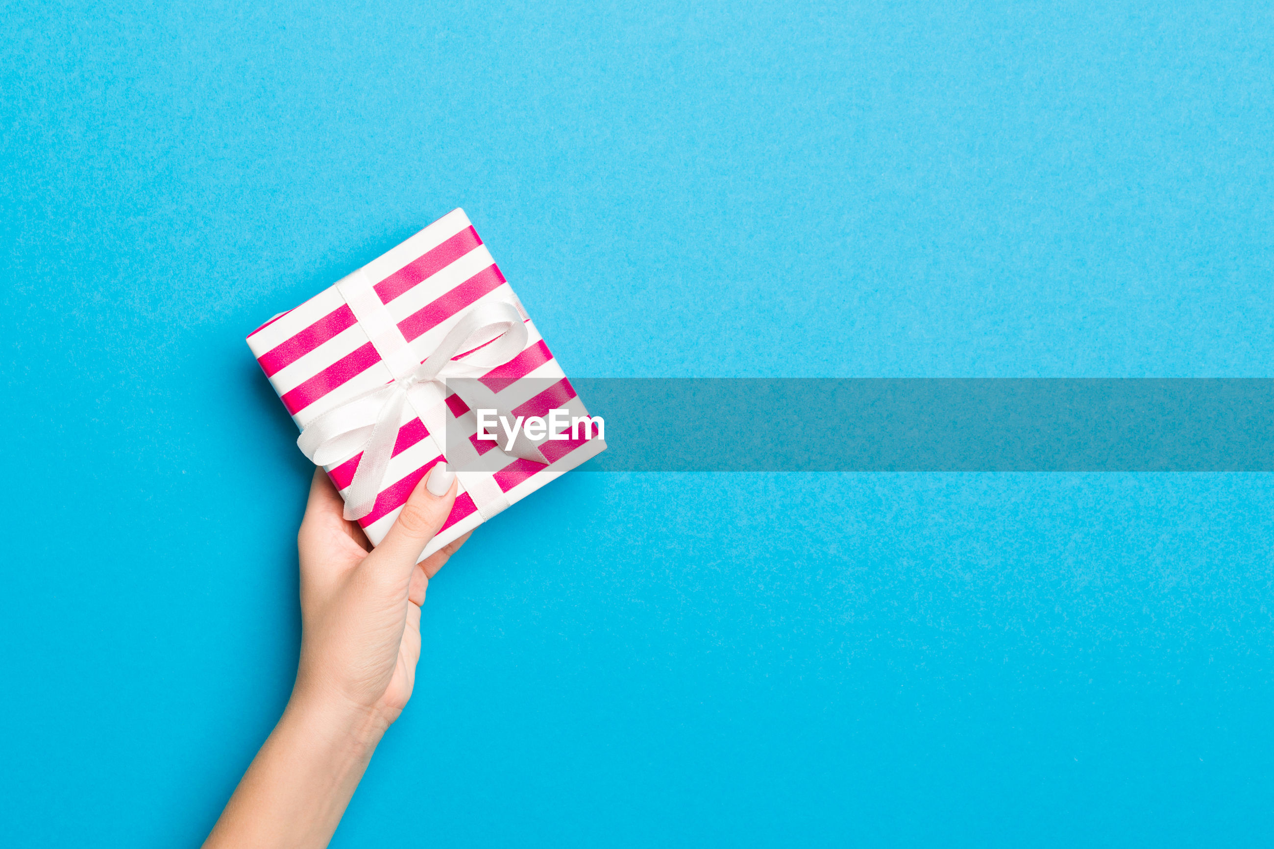 Cropped hands holding multi colored gift against colored background