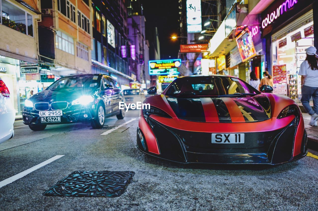 city, mode of transportation, transportation, night, illuminated, car, building exterior, built structure, architecture, motor vehicle, street, land vehicle, incidental people, sign, communication, road, text, city life, western script, city street