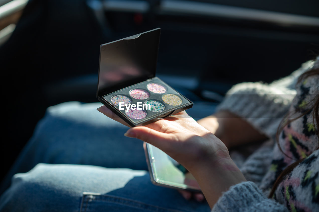 A girl sitting in a car looking at a new palette of eyeshadow. close-up of person using phone.