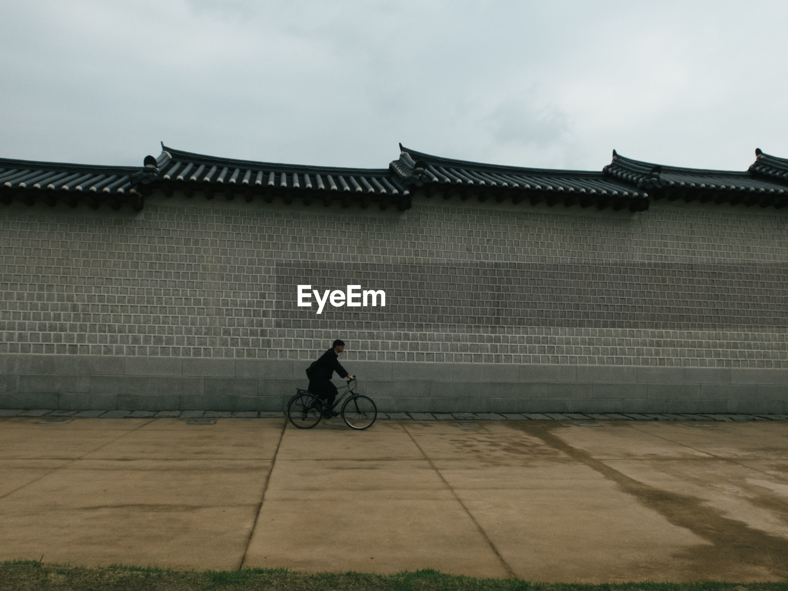MAN CYCLING ON BICYCLE AGAINST BUILDING