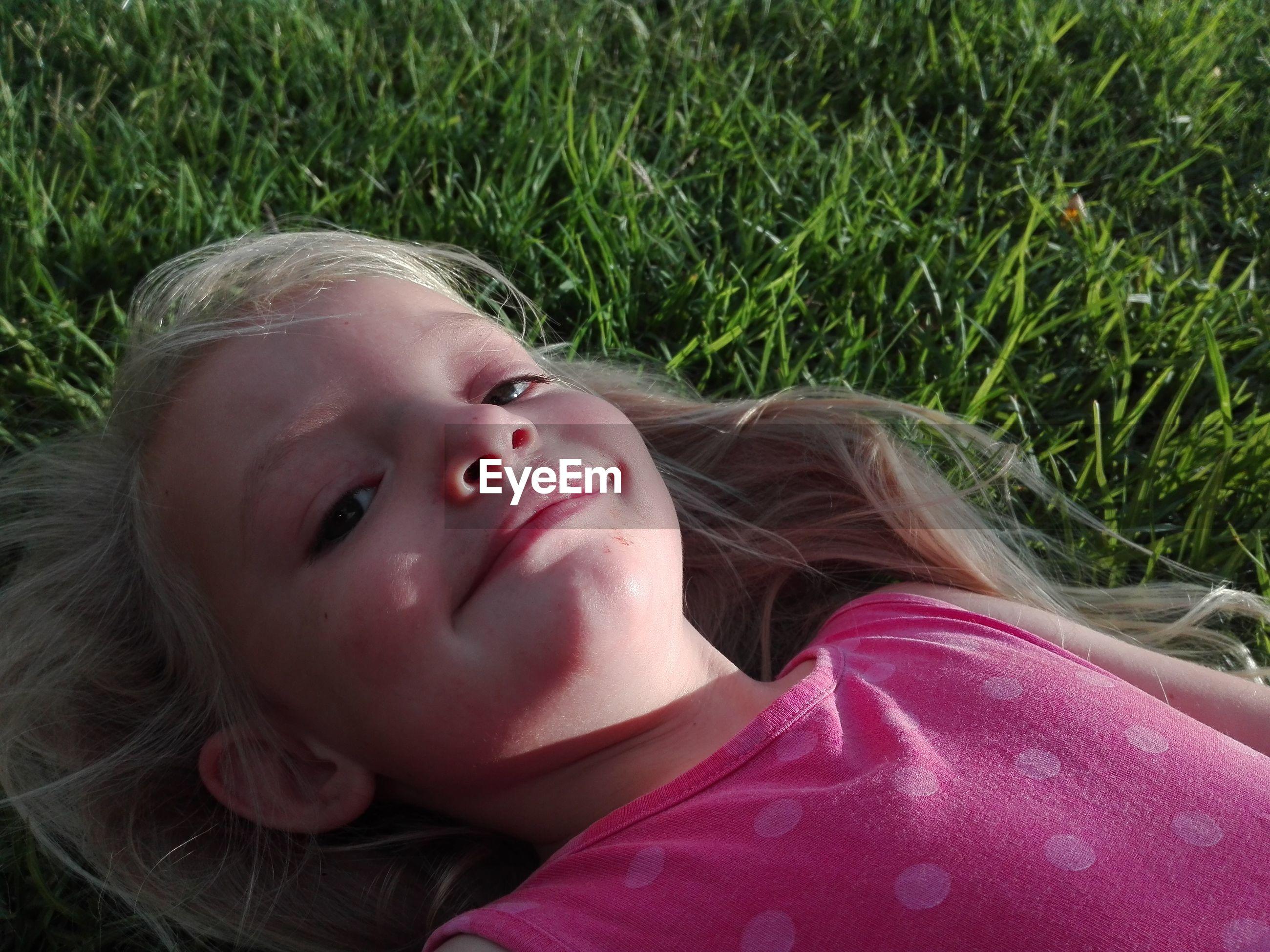 Portrait of cute girl relaxing on field
