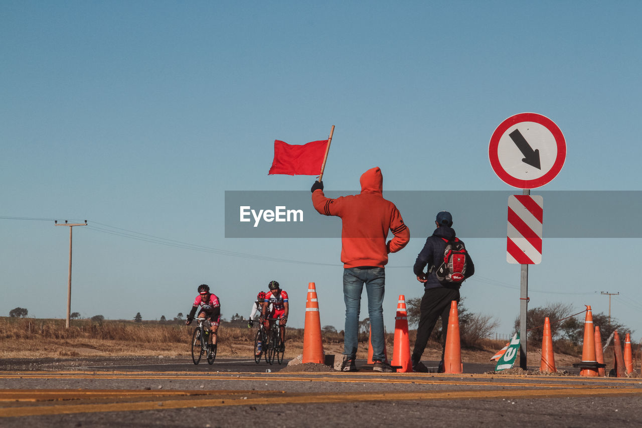 Rear view of man holding red flag while cyclists riding bicycles on road against clear sky