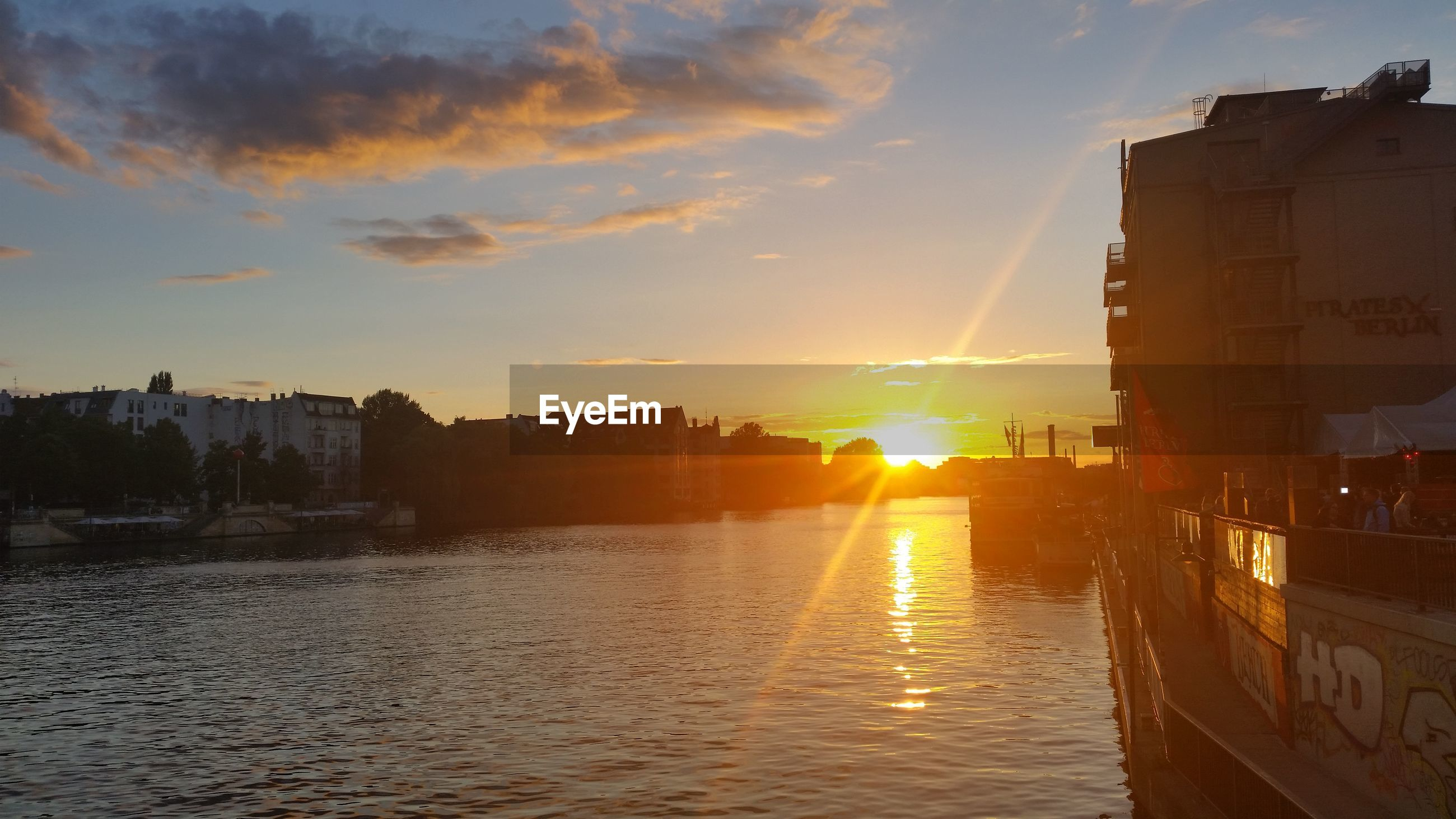 building exterior, architecture, built structure, sunset, water, sun, city, river, sunlight, waterfront, sunbeam, residential structure, canal, lens flare, building, sky, orange color, city life, cityscape, residential district, outdoors, shining, scenics, bright, no people, sea, cloud - sky