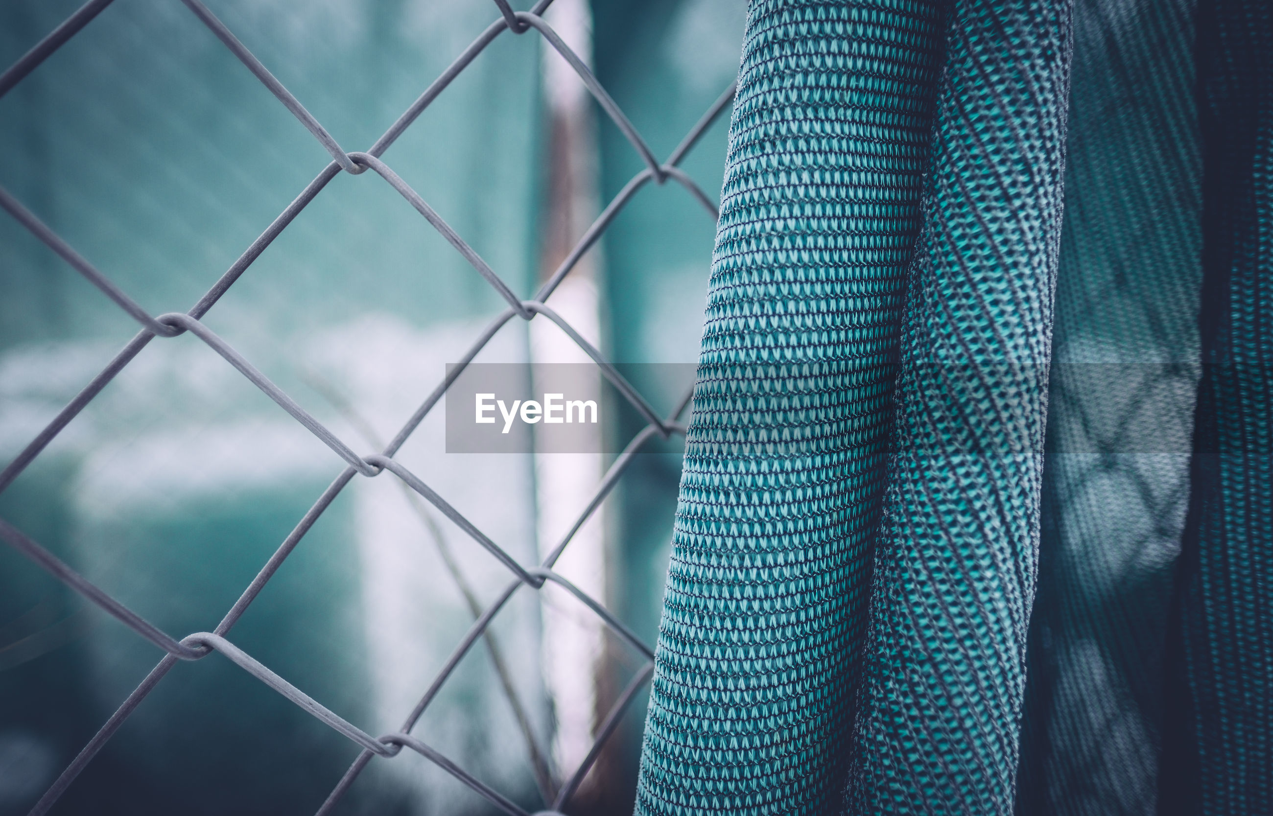 Close-up of fabric on chainlink fence