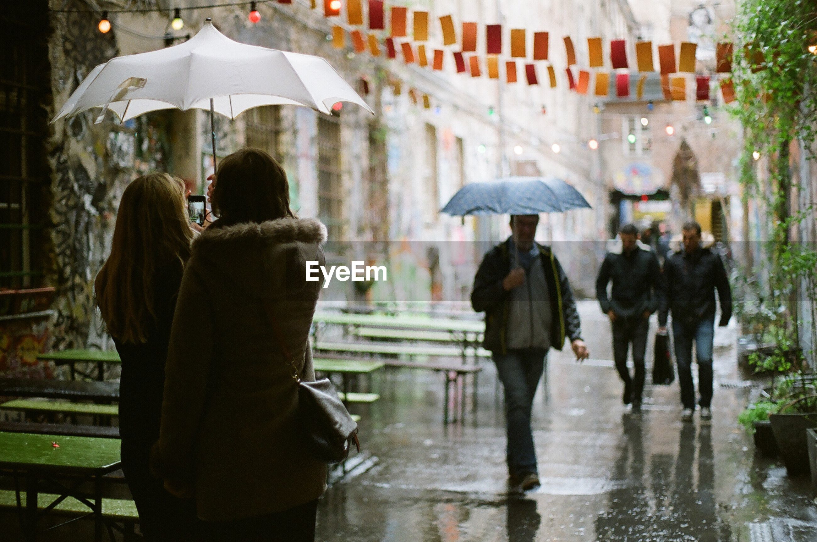 REAR VIEW OF PEOPLE IN WET RAIN