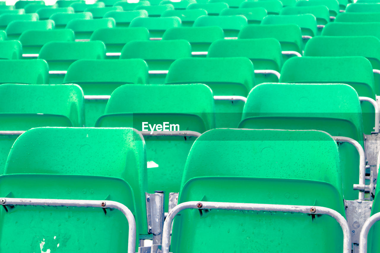 in a row, green color, full frame, empty, seat, backgrounds, chair, repetition, abundance, large group of objects, conformity, no people, arrangement, day, folding chair, outdoors, stadium