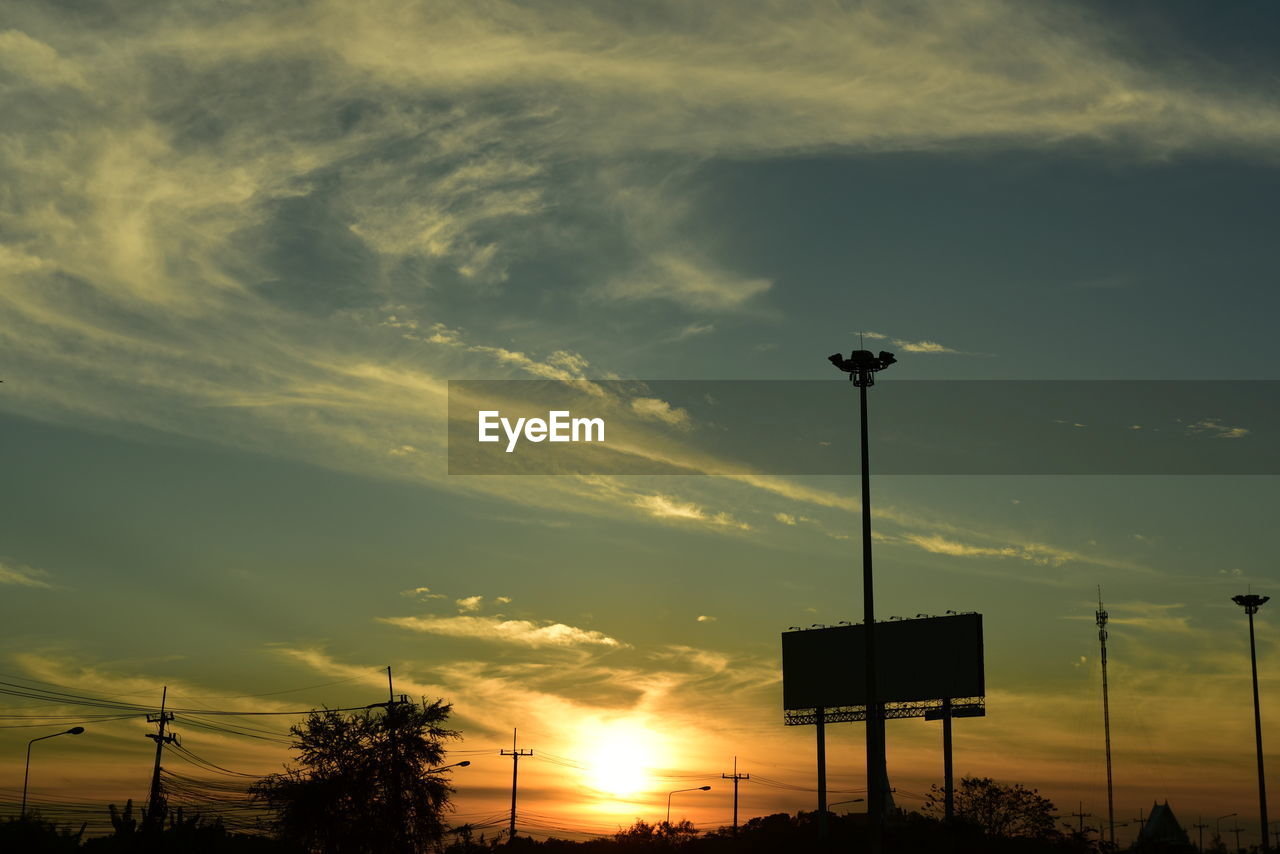 sky, sunset, cloud - sky, silhouette, low angle view, beauty in nature, orange color, nature, lighting equipment, street light, no people, street, technology, outdoors, scenics - nature, tree, plant, floodlight, tranquility, electricity, power supply