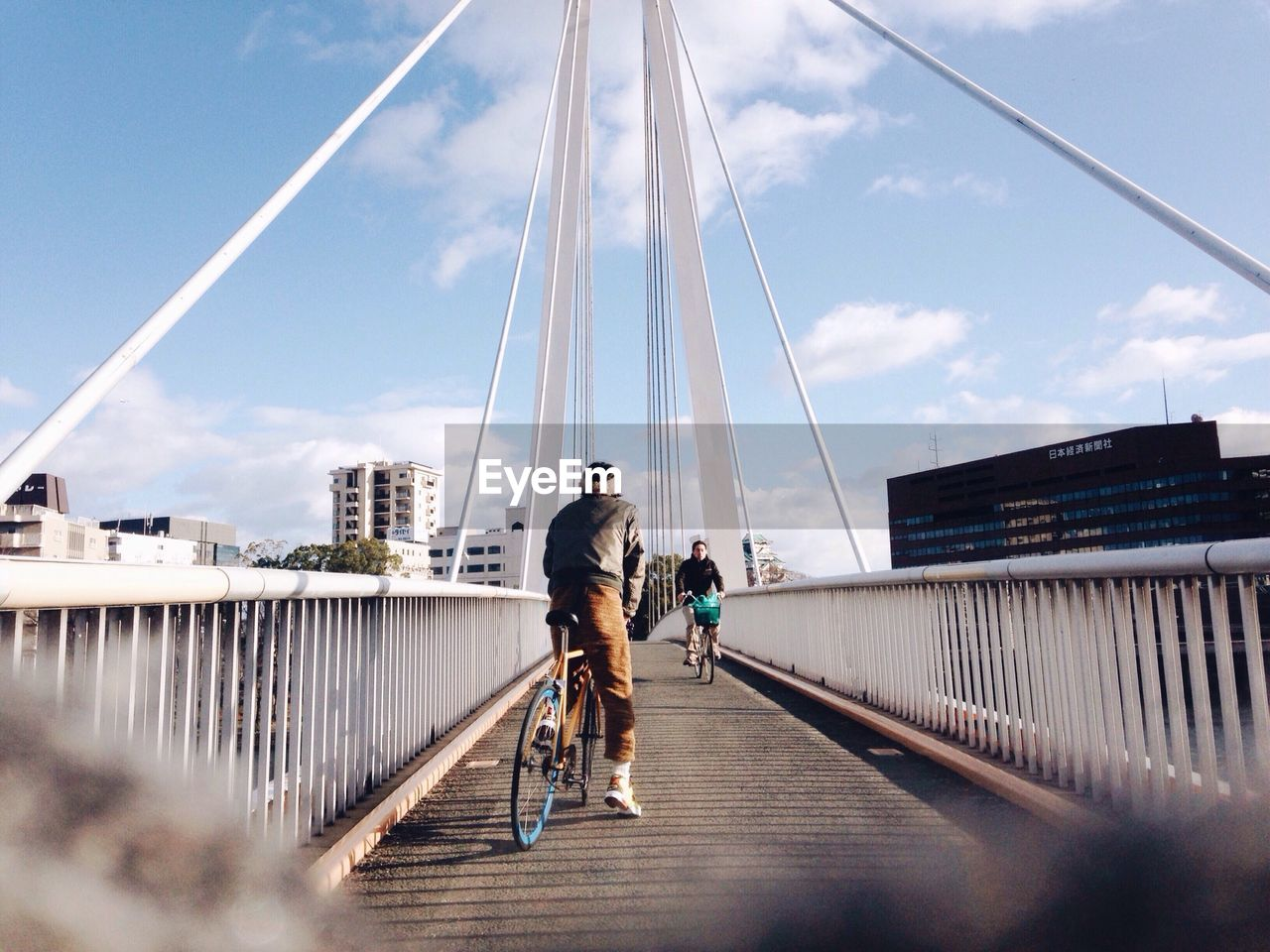 bicycle, sky, transportation, mode of transport, full length, day, cycling, bridge - man made structure, lifestyles, outdoors, togetherness, leisure activity, land vehicle, men, built structure, two people, cycling helmet, real people, city, architecture, footbridge, sports clothing, friendship, nature, people