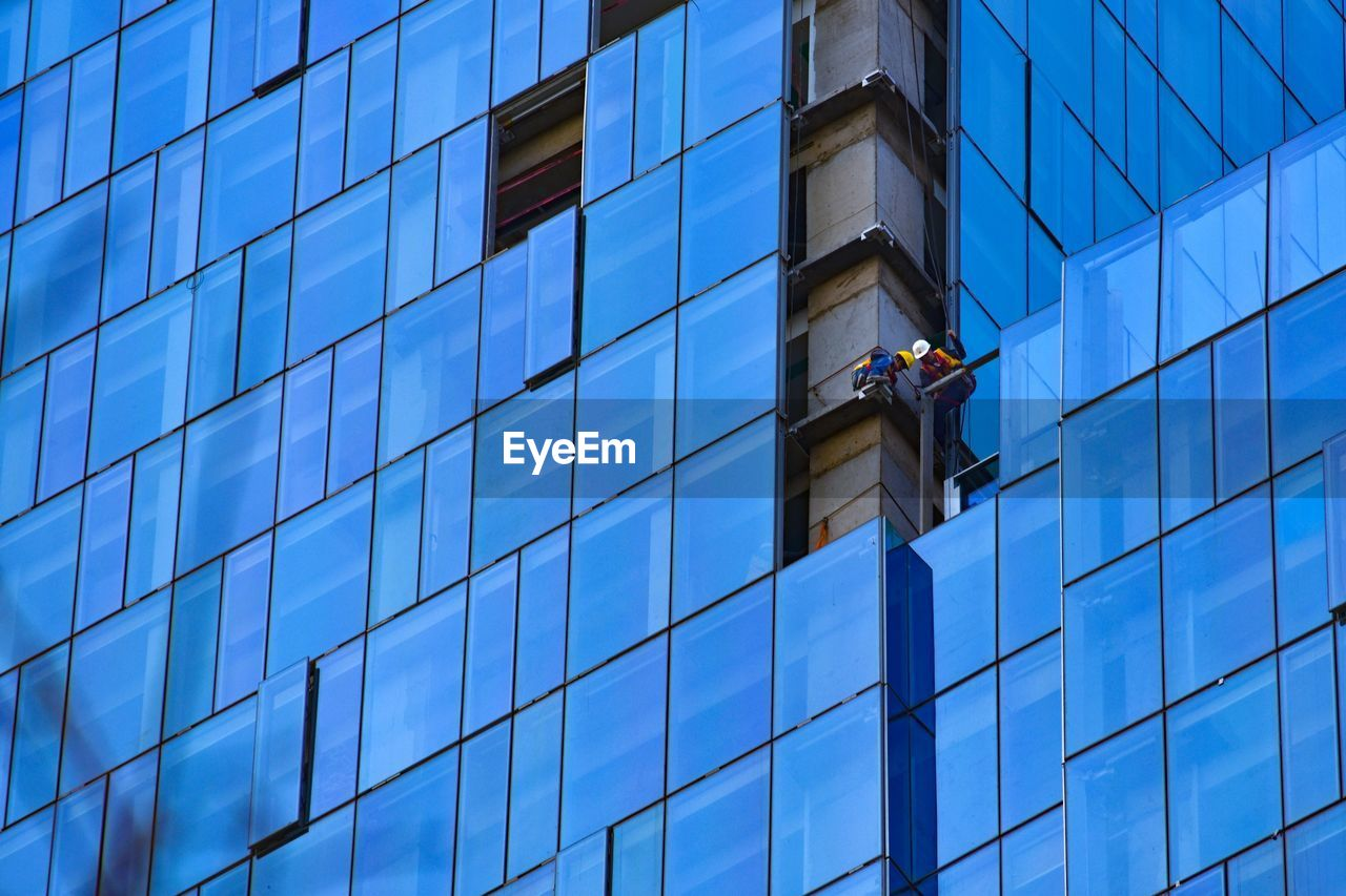 Low Angle View Of Worker Repairing Office Building