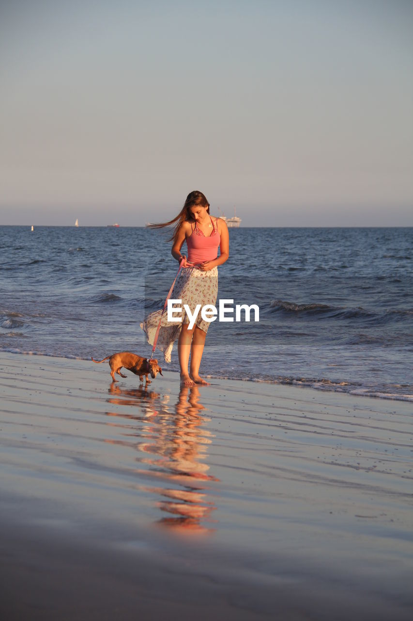 Young woman with dog standing at beach