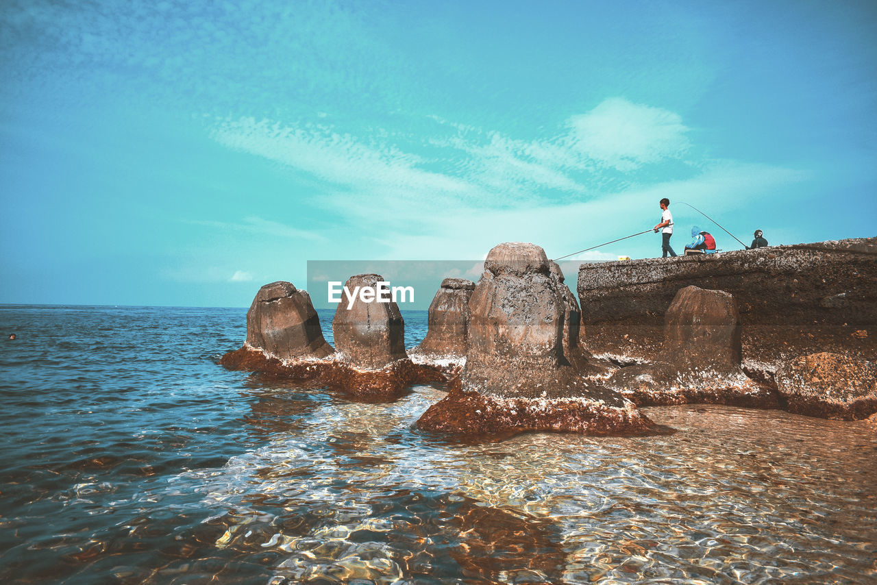 water, sea, real people, waterfront, lifestyles, sky, beauty in nature, rock, men, scenics - nature, rock - object, leisure activity, solid, nature, one person, day, blue, tranquility, horizon over water, outdoors
