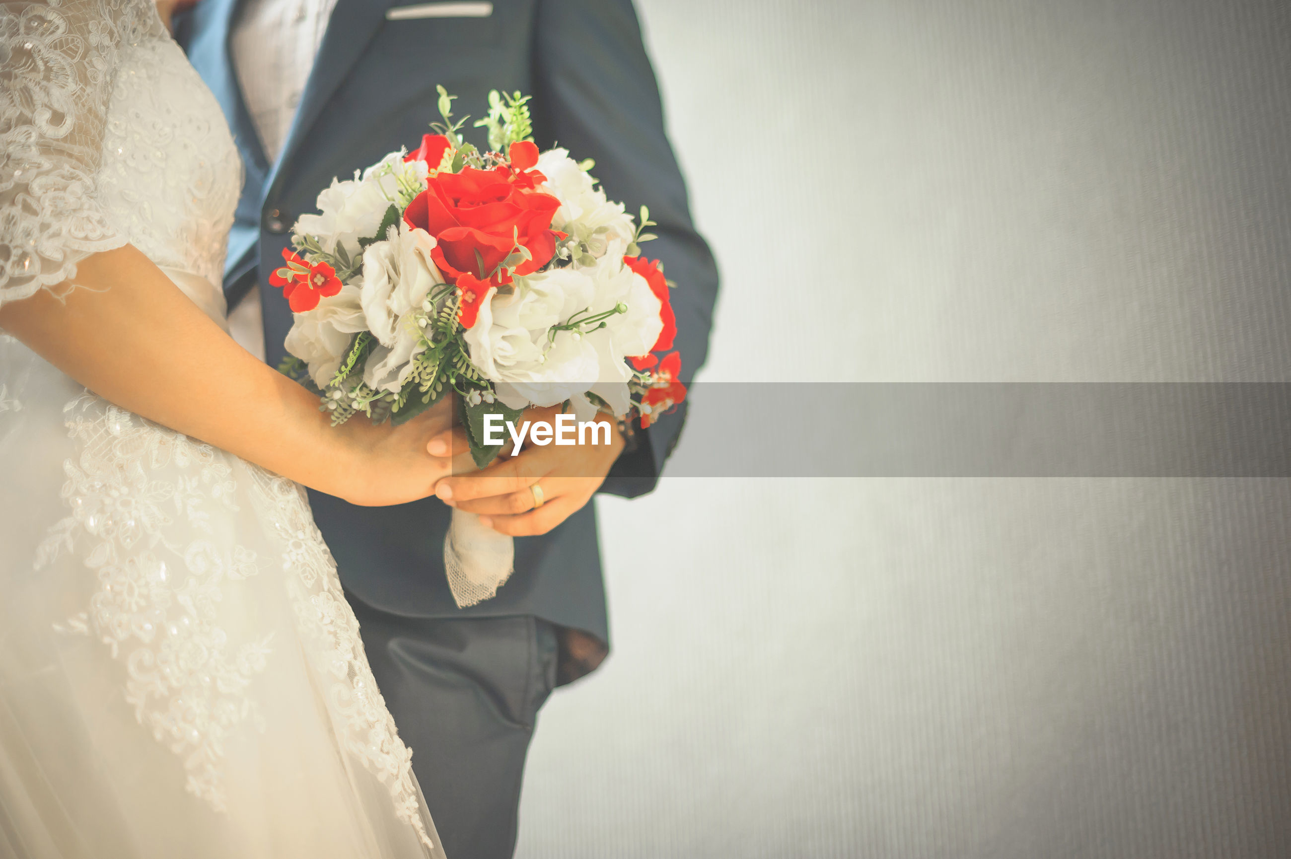 Midsection of bride and bridegroom holding bouquet against wall