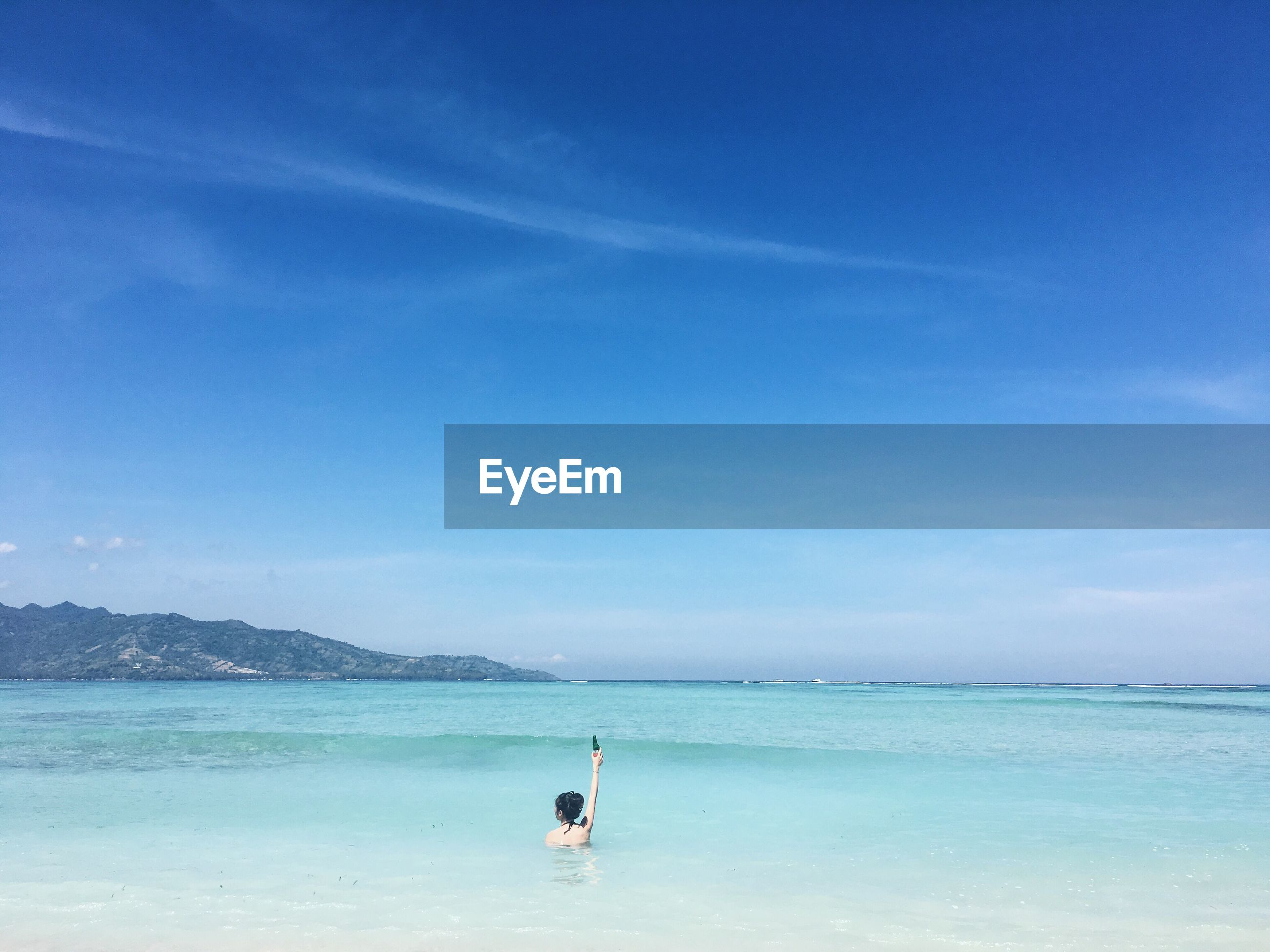 Woman swimming in sea against blue sky