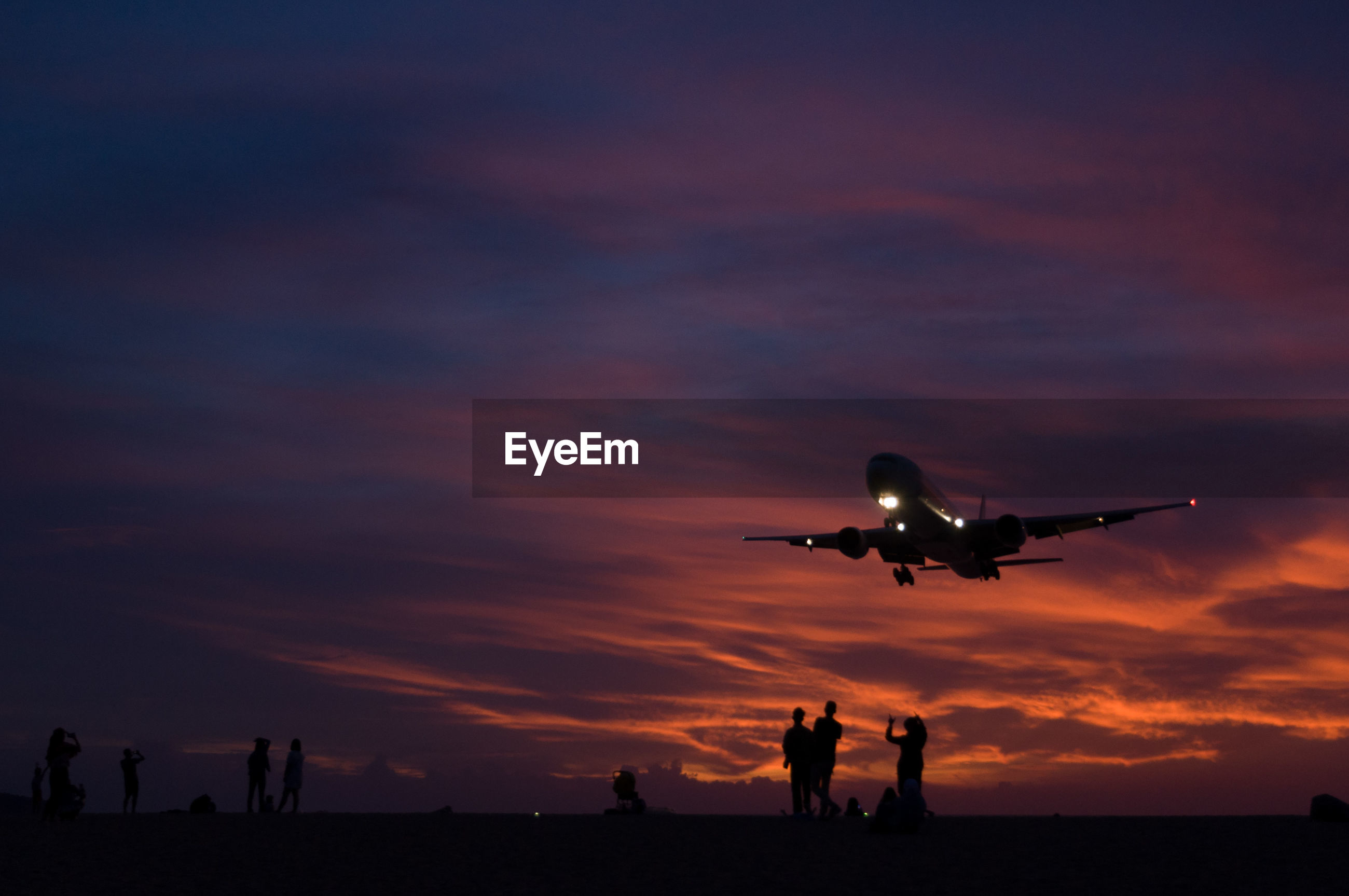 Silhouette of people standing while airplane flying in sky at dusk