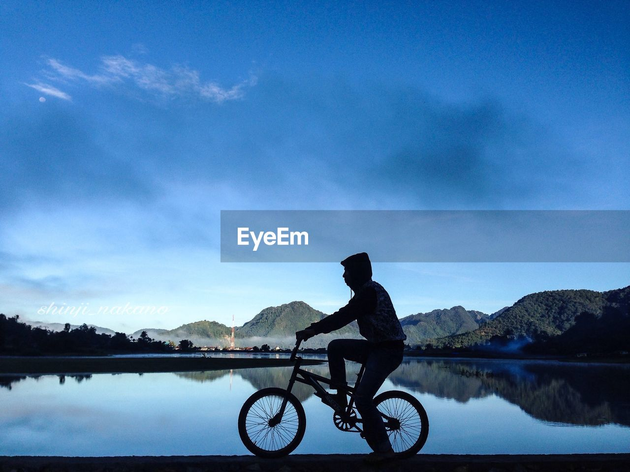Silhouette man riding bicycle by lake against sky
