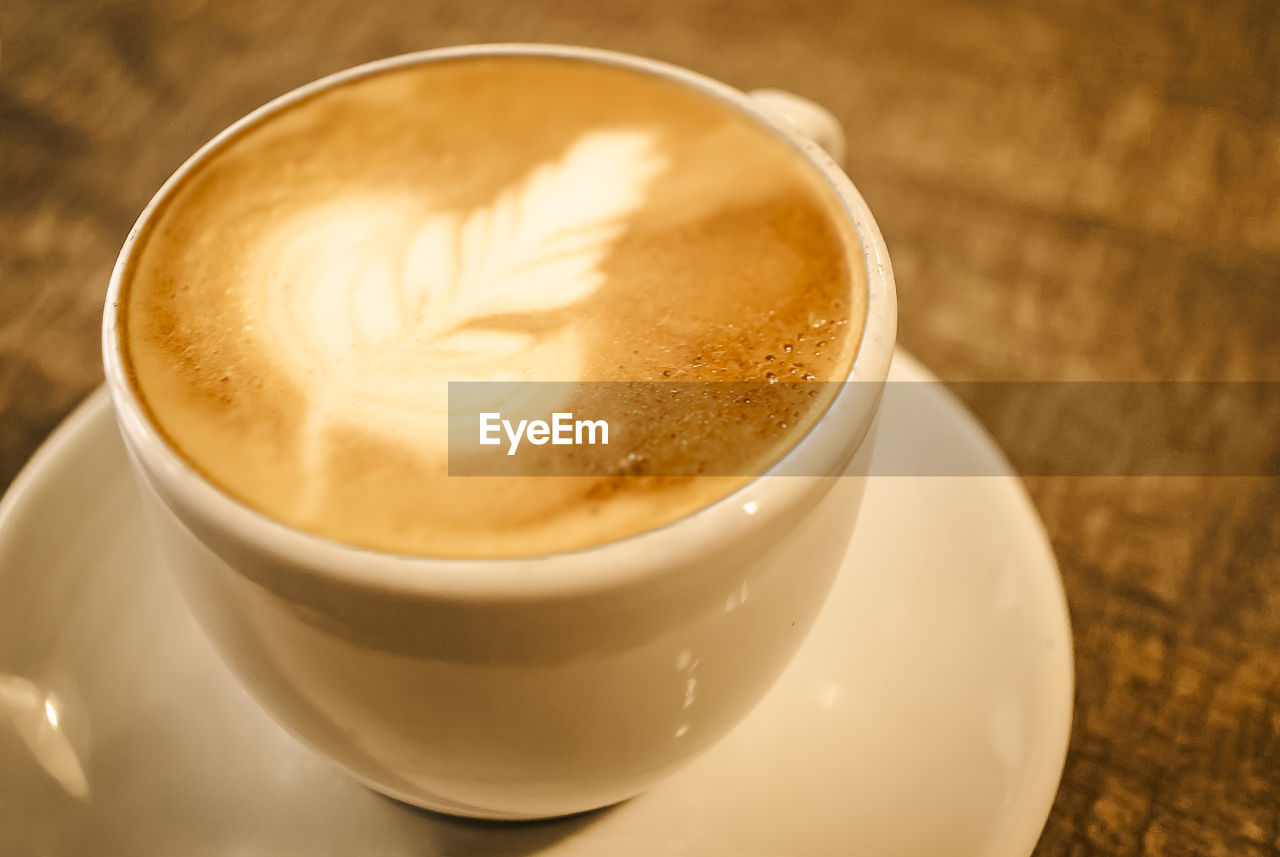 Close-Up Of Coffee With Froth Art On Table