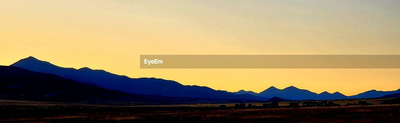 sky, sunset, mountain, scenics - nature, beauty in nature, tranquil scene, mountain range, tranquility, silhouette, no people, nature, idyllic, non-urban scene, orange color, copy space, landscape, environment, outdoors, land, clear sky, mountain peak