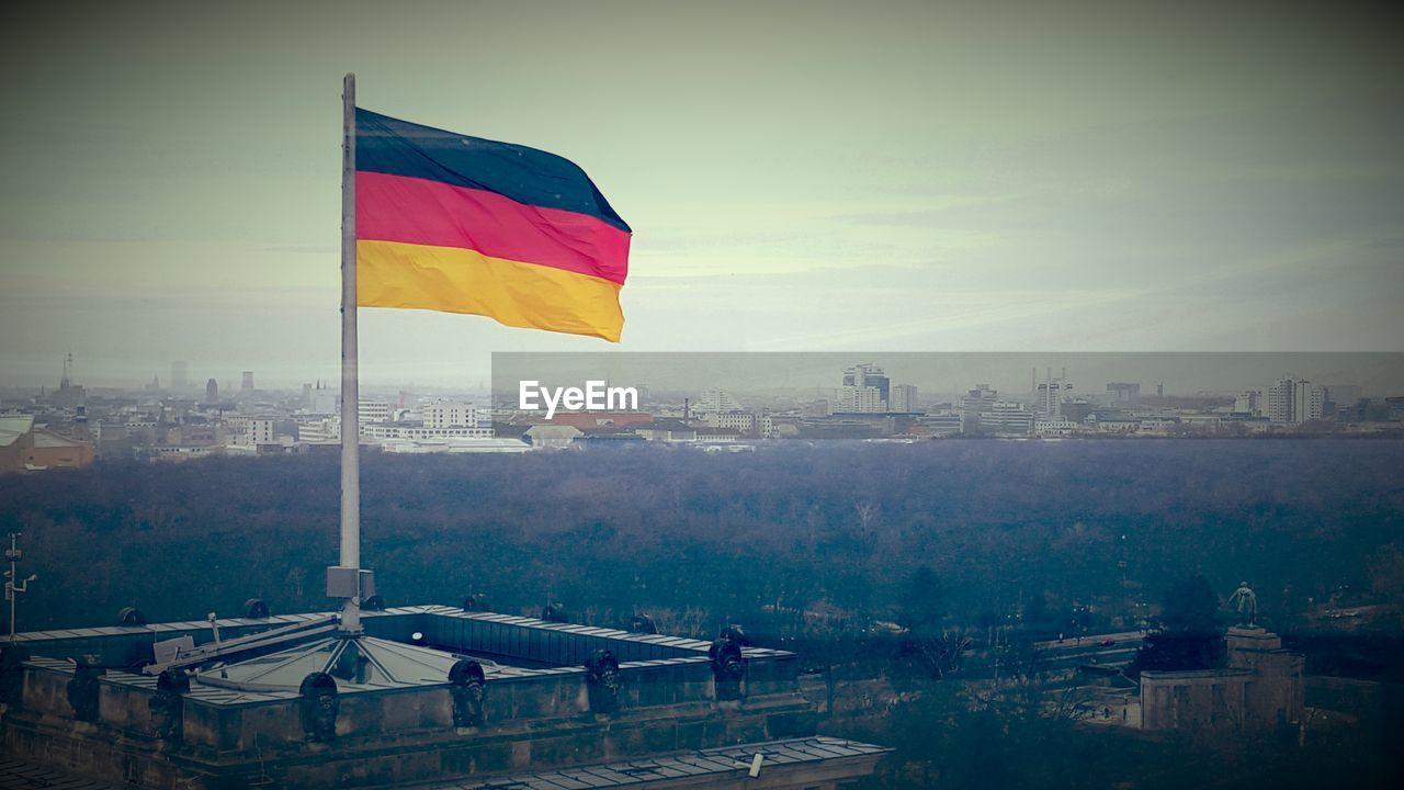 flag, no people, day, outdoors, architecture, built structure, sky, patriotism, building exterior, cityscape, nature, city