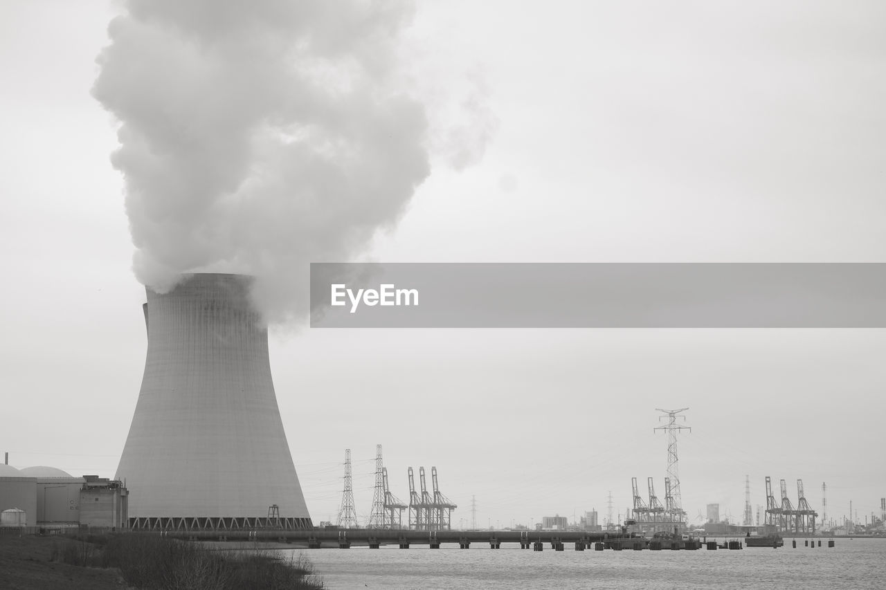 pollution, environmental issues, smoke stack, factory, smoke - physical structure, environment, sky, building exterior, emitting, built structure, fuel and power generation, industry, architecture, chimney, power station, air pollution, no people, environmental damage, nature, day, fumes, outdoors, ecosystem, cooling tower, atmospheric