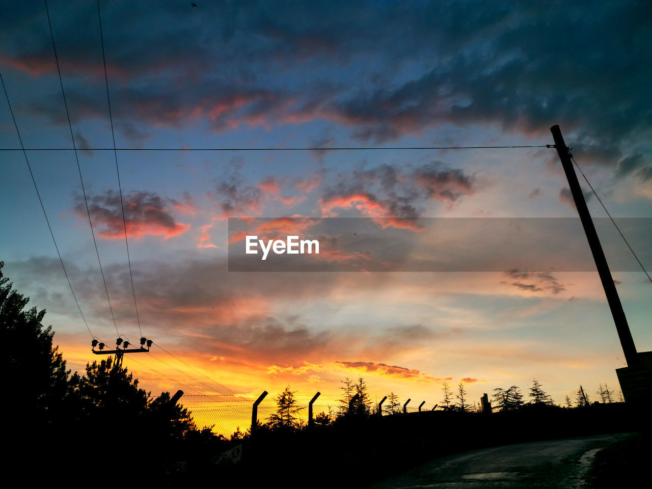 sky, cloud - sky, sunset, beauty in nature, silhouette, orange color, tranquility, tranquil scene, scenics - nature, cable, plant, tree, nature, no people, idyllic, electricity, power line, dramatic sky, technology, low angle view, outdoors, power supply, telephone line