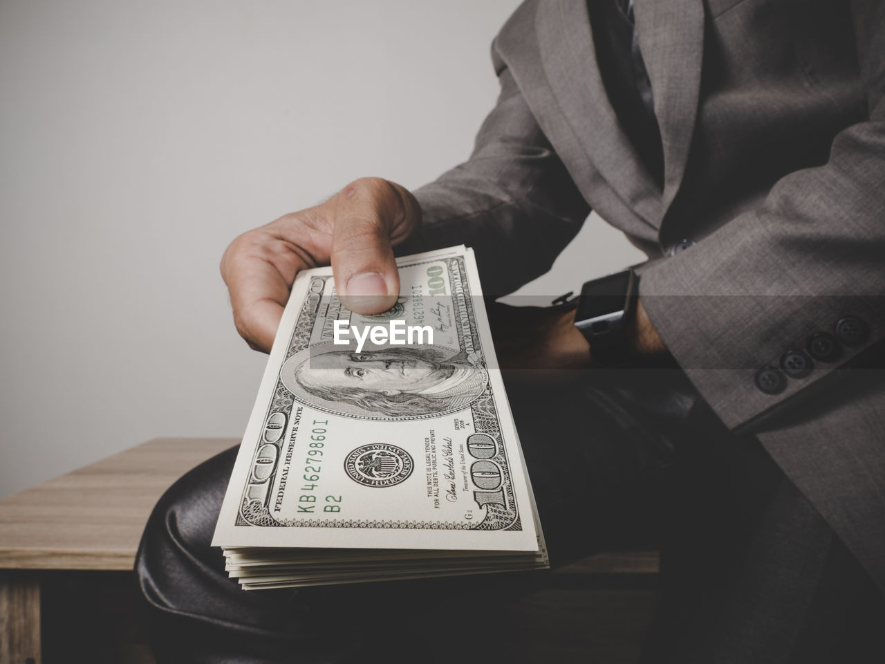 Midsection Of Businessman Holding Paper Currencies Sitting On Table