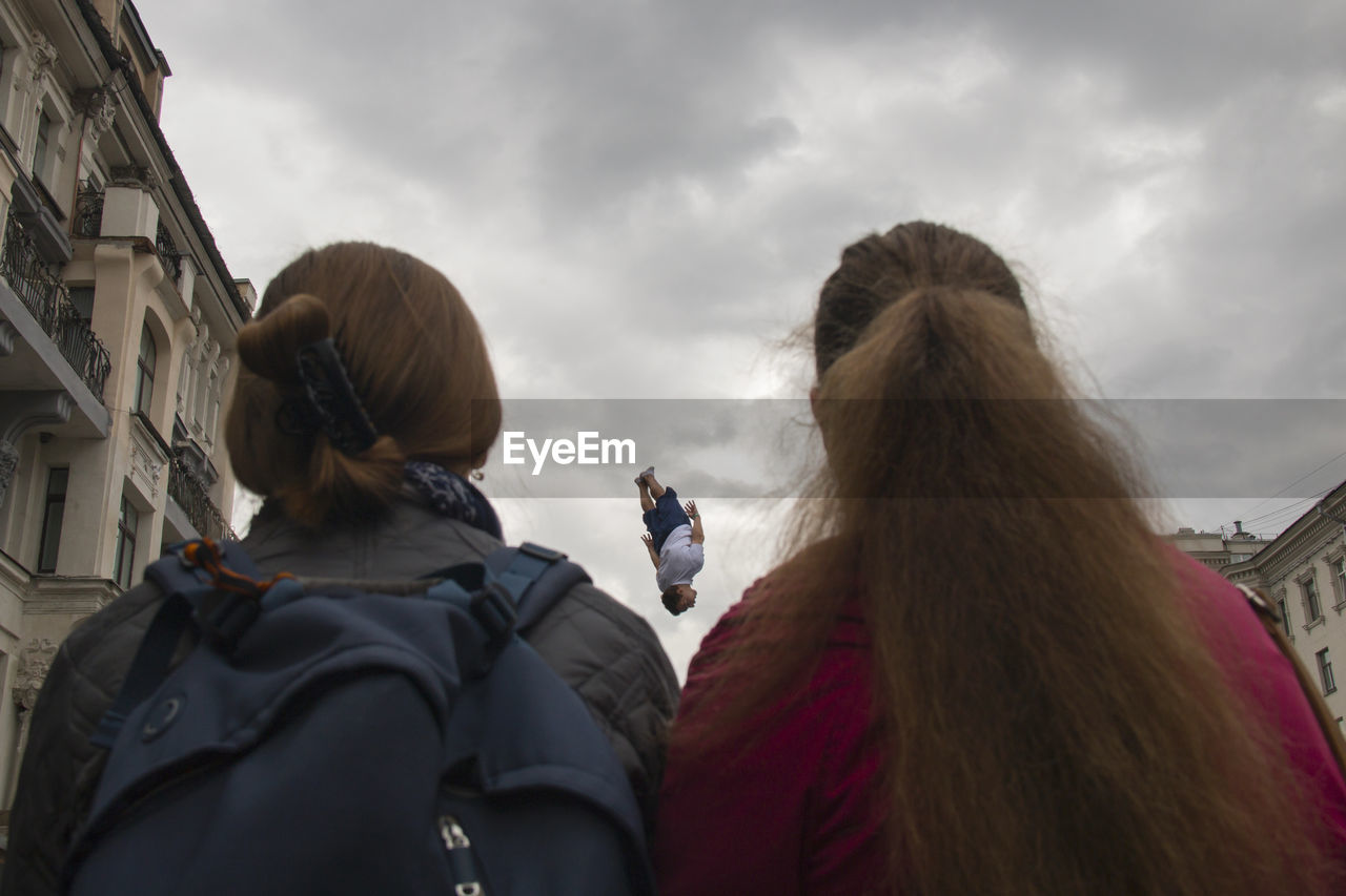 rear view, real people, cloud - sky, sky, two people, leisure activity, togetherness, day, built structure, low angle view, outdoors, friendship, women, lifestyles, girls, headshot, building exterior, childhood, architecture, young women, domestic animals, nature, warm clothing, young adult, mammal, adult, people