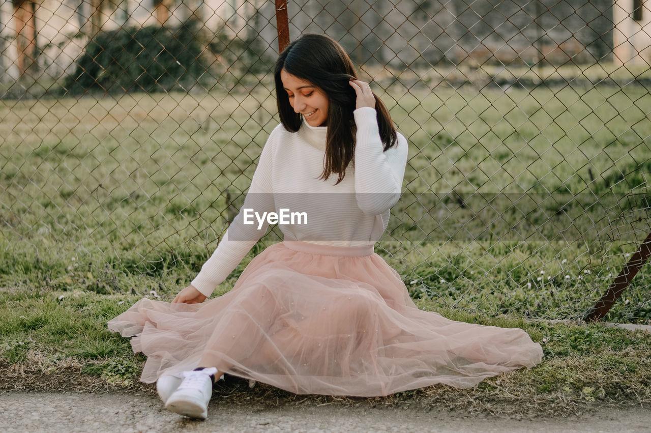 Full length of beautiful young woman lying on land, long princess pink skirt