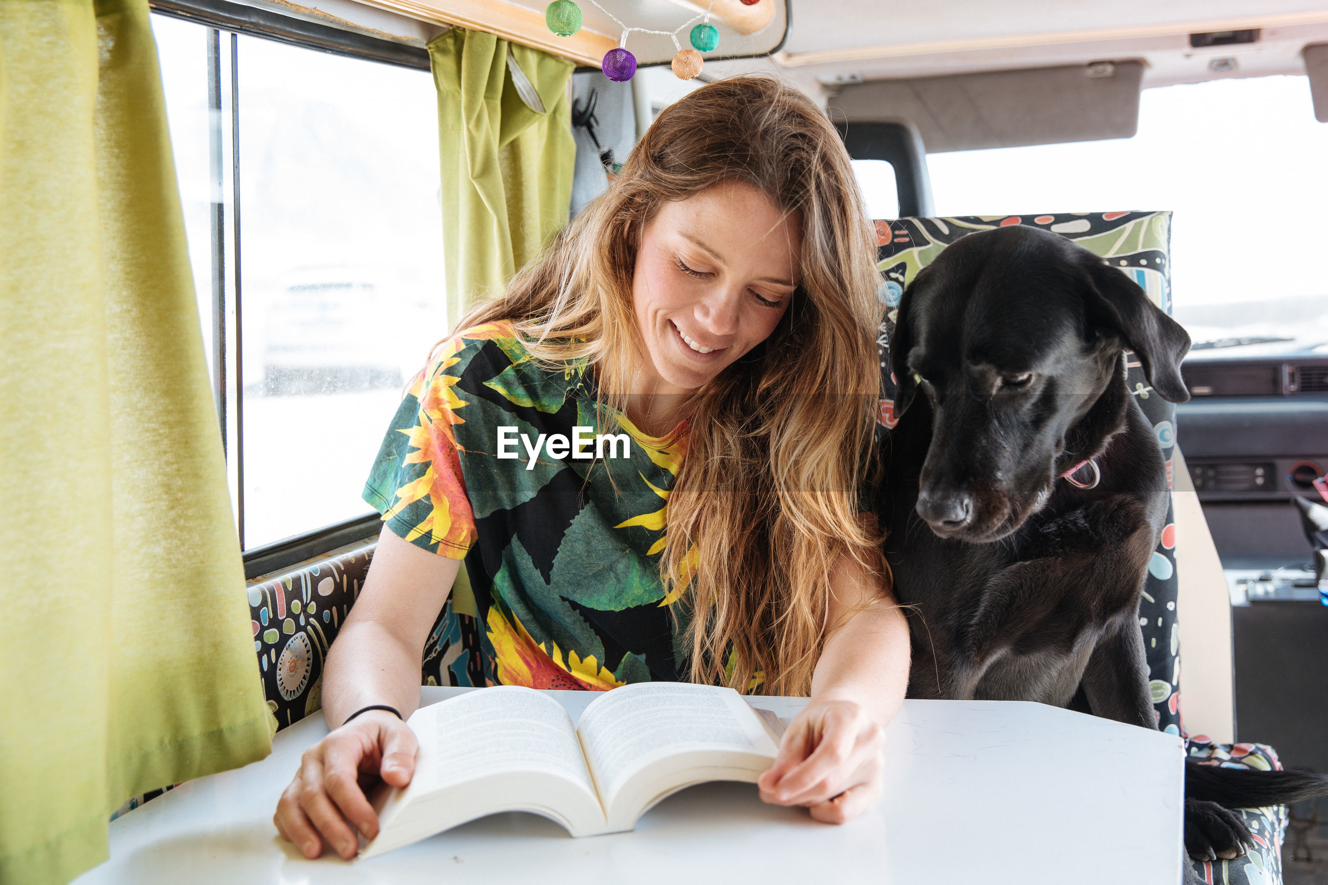 Woman traveling with dog in camper van