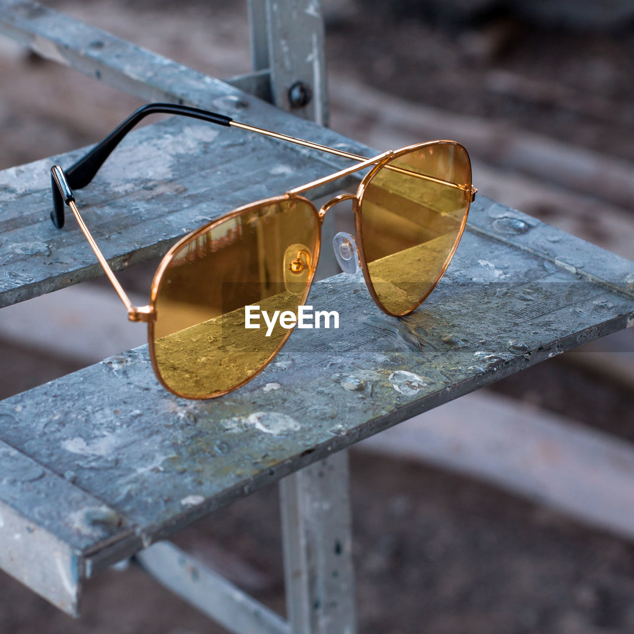 close-up, focus on foreground, metal, no people, day, wood - material, high angle view, glasses, still life, outdoors, security, protection, water, old, communication, nature, sunglasses, yellow, fashion, personal accessory