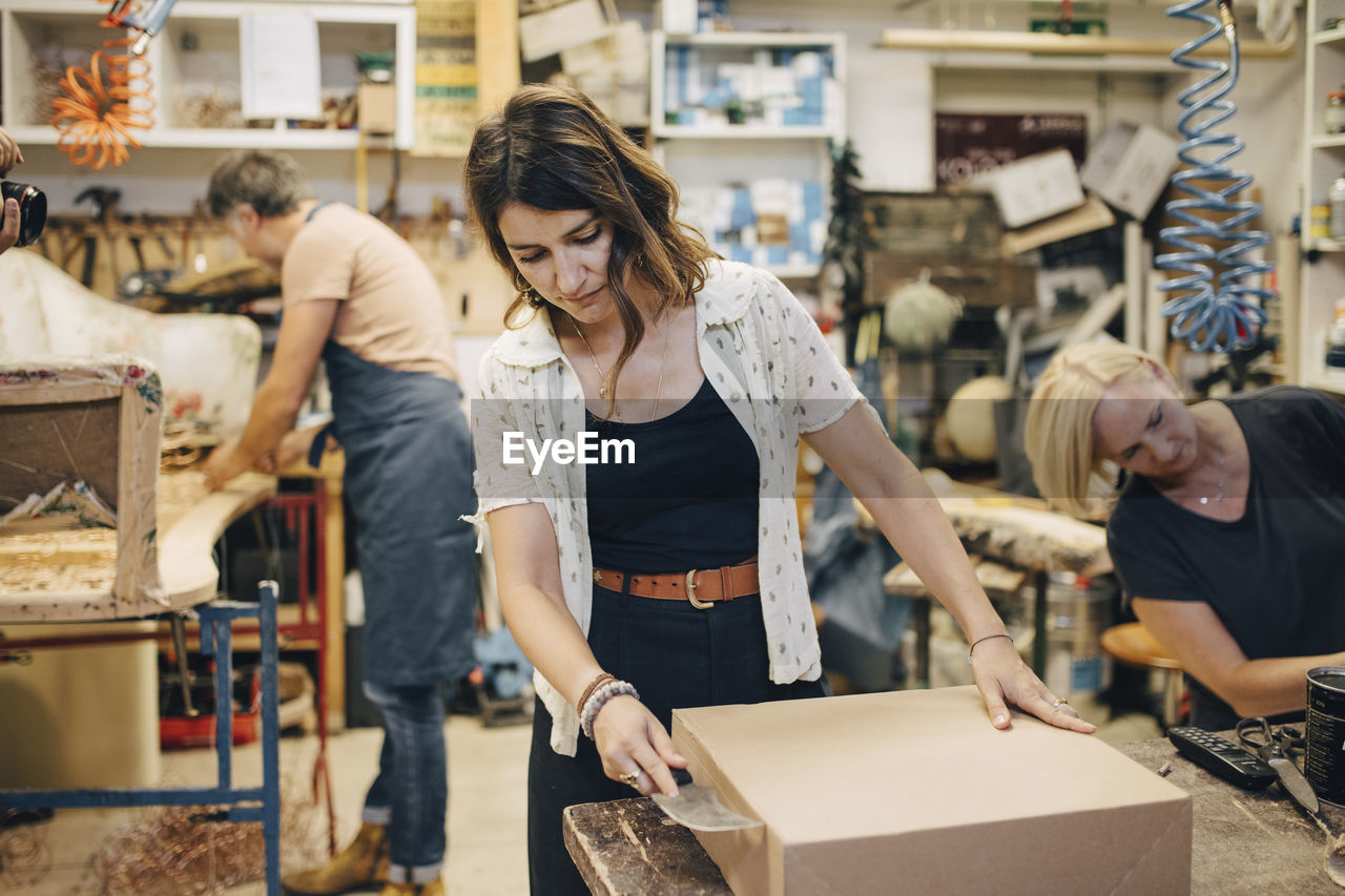 occupation, working, women, indoors, real people, standing, small business, front view, workshop, three quarter length, focus on foreground, casual clothing, young adult, business, apron, young women, adult, females, two people, teamwork, coworker